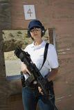 Mujer que sostiene la ametralladora en la gama de leña Foto de archivo libre de regalías