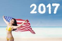 Mujer que sostiene la bandera americana en la playa Imagen de archivo libre de regalías