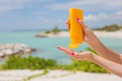 Mujer que sostiene la botella amarilla de la protección solar en manos Fotos de archivo