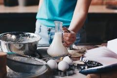 Mujer que sostiene la botella con leche mientras que cuece Foto de archivo libre de regalías