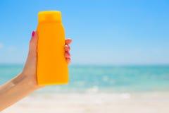 Mujer que sostiene la botella de la protección solar fotografía de archivo