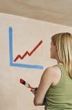Mujer que sostiene la brocha con el diagrama pintado en la pared imagen de archivo