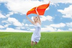Mujer que sostiene la bufanda que corre en campo Imagen de archivo