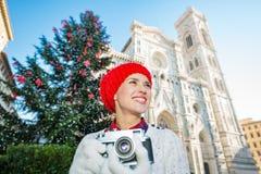 Mujer que sostiene la cámara de la foto cerca del árbol de navidad en Florencia Fotografía de archivo