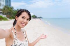 Mujer que sostiene la cámara para tomar el selfie en la playa Fotos de archivo