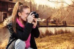 Mujer que sostiene la cámara y que toma la foto afuera Imagen de archivo libre de regalías