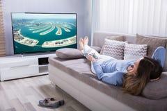 Mujer que sostiene la calculadora mientras que mira la televisión fotos de archivo libres de regalías