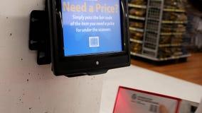 Mujer que sostiene la caldera para comprobar precio en el escáner de código de barras almacen de metraje de vídeo