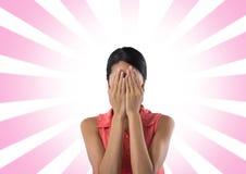 Mujer que sostiene la cara en manos con el fondo rosado radial imagen de archivo