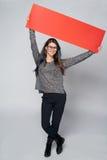 Mujer que sostiene la cartulina en blanco roja Imagen de archivo