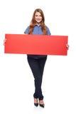 Mujer que sostiene la cartulina en blanco roja Imagenes de archivo