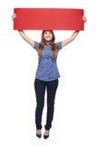 Mujer que sostiene la cartulina en blanco roja Fotografía de archivo libre de regalías
