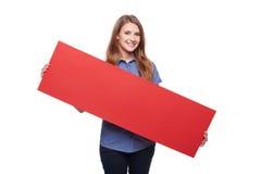 Mujer que sostiene la cartulina en blanco roja Fotografía de archivo