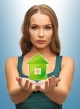 Mujer que sostiene la casa verde en sus manos Imagen de archivo libre de regalías