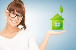 Mujer que sostiene la casa verde en sus manos Imágenes de archivo libres de regalías