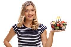 Mujer que sostiene la cesta llena de frutas y verduras Fotos de archivo