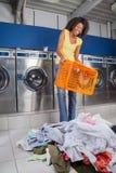 Mujer que sostiene la cesta vacía con ropa en piso Imagenes de archivo