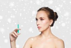 Mujer que sostiene la jeringuilla con la inyección sobre nieve Foto de archivo