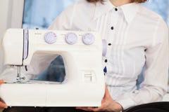 Mujer que sostiene la máquina de coser Fotos de archivo