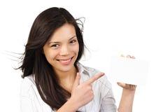 Mujer que sostiene la muestra/la tarjeta del papel en blanco Fotografía de archivo libre de regalías