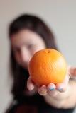 Mujer que sostiene la naranja Fotos de archivo libres de regalías