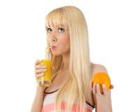 Mujer que sostiene la naranja mientras que sorbe el vidrio de jugo Fotos de archivo
