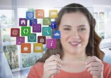 Mujer que sostiene la pantalla de cristal con los apps por la ventana soleada imágenes de archivo libres de regalías