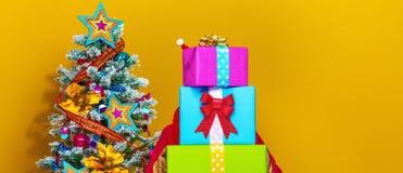 Mujer que sostiene la pila de cajas del regalo de Navidad Imagen de archivo libre de regalías