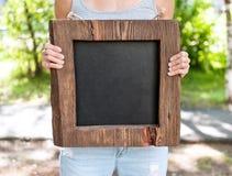 Mujer que sostiene la pizarra vacía con el marco de madera Mofa de la plantilla Fotos de archivo