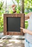 Mujer que sostiene la pizarra vacía con el marco de madera Mofa de la plantilla Fotos de archivo libres de regalías
