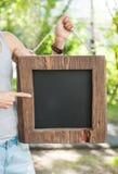 Mujer que sostiene la pizarra vacía con el marco de madera Mofa de la plantilla Imágenes de archivo libres de regalías