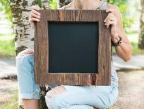 Mujer que sostiene la pizarra vacía con el marco de madera Mofa de la plantilla Fotografía de archivo
