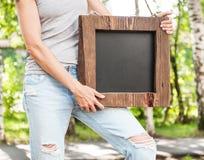 Mujer que sostiene la pizarra vacía con el marco de madera Mofa de la plantilla Imagen de archivo libre de regalías