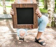 Mujer que sostiene la pizarra vacía con el marco de madera Mofa de la plantilla Fotografía de archivo libre de regalías