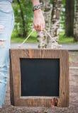 Mujer que sostiene la pizarra vacía con el marco de madera Mofa de la plantilla Foto de archivo libre de regalías