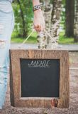 Mujer que sostiene la pizarra vacía con el marco de madera Mofa de la plantilla Foto de archivo