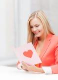 Mujer que sostiene la postal con forma del corazón Imagenes de archivo