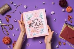 Mujer que sostiene la postal feliz del día de madres en manos con las decoraciones alrededor en púrpura foto de archivo