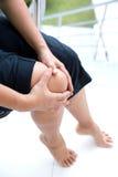 Mujer que sostiene la rodilla derecha con ambas manos mientras que se sienta para mostrar dolor en la rodilla Imágenes de archivo libres de regalías