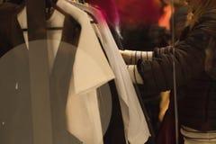 Mujer que sostiene la ropa en una tienda durante compras Foto de archivo libre de regalías