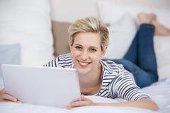 Mujer que sostiene la tableta de Digitaces mientras que miente en cama Imagenes de archivo