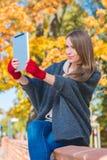 Mujer que sostiene la tableta del ordenador al aire libre en otoño imágenes de archivo libres de regalías
