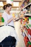 Mujer que sostiene la tablilla digital en centro comercial Imagen de archivo