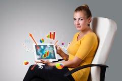 Mujer que sostiene la tablilla moderna con los diagramas y los gráficos coloridos Fotos de archivo libres de regalías