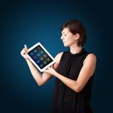 Mujer que sostiene la tablilla moderna con los iconos coloridos Imagen de archivo