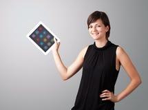 Mujer que sostiene la tablilla moderna con los iconos coloridos Foto de archivo