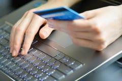Mujer que sostiene la tarjeta de crédito en el ordenador portátil para el concepto en línea de las compras Imagenes de archivo