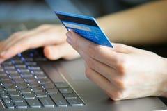 Mujer que sostiene la tarjeta de crédito en el ordenador portátil para el concepto en línea de las compras Fotografía de archivo
