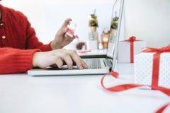 Mujer que sostiene la tarjeta de crédito y que hace compras en línea Imagen de archivo libre de regalías