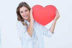 Mujer que sostiene la tarjeta del corazón Fotos de archivo libres de regalías